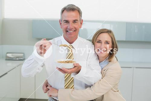 Woman embracing man while having breakfast in kitchen