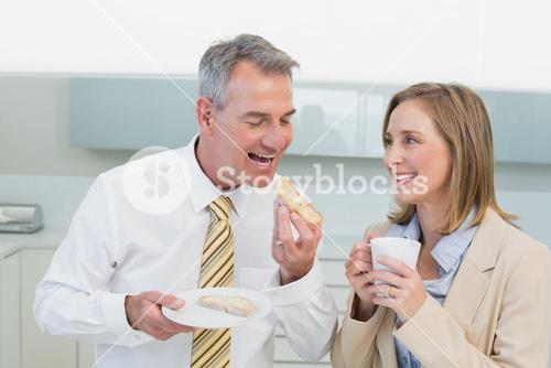 Happy business couple having breakfast in kitchen