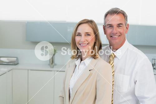 Portrait of a business couple standing in kitchen