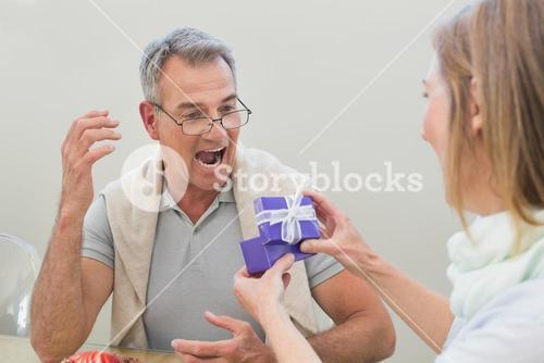 Shocked man receiving gift by woman