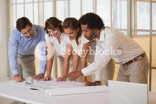 Architects working on blueprints at office