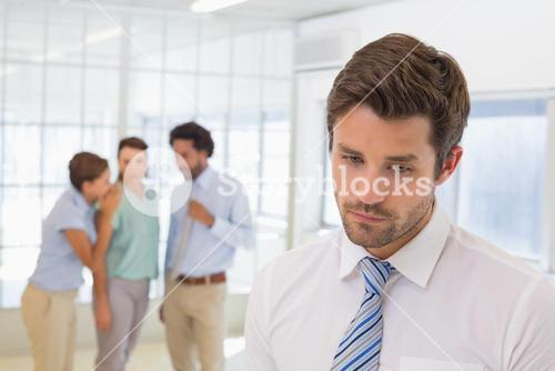 Colleagues gossiping with sad businessman in foreground