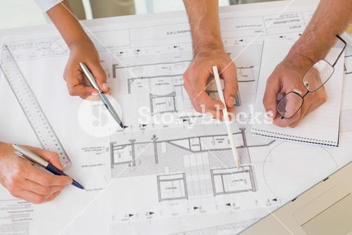 Several hands working on blueprints
