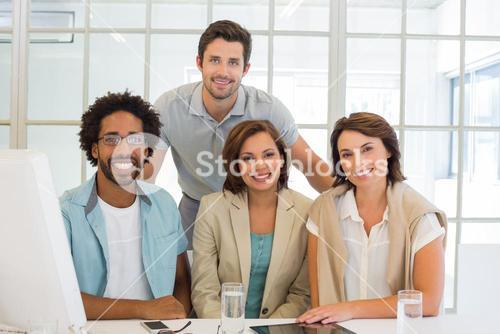 Business people smiling at office desk