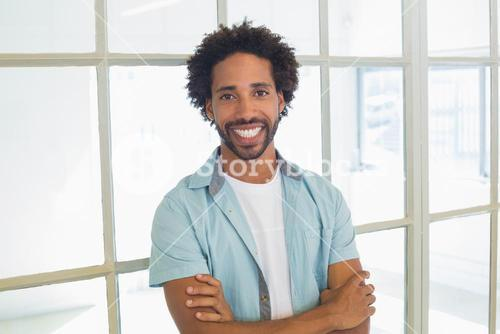 Smiling casual businessman with arms crossed in office