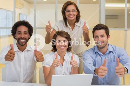 Happy business people gesturing thumbs up at office