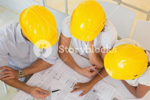 Architects in yellow helmets working on blueprints at office