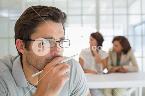 Serious businessman with colleagues in meeting at office