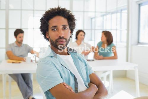 Portrait of a serious businessman with colleagues in meeting