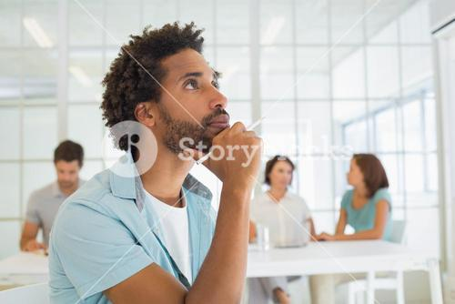 Close-up of serious businessman with colleagues in meeting