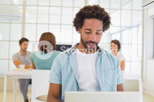 Businessman using laptop with colleagues in meeting