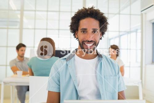 Portrait of a smiling businessman with colleagues in meeting