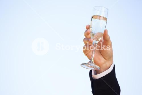 Hand raising champagne glass against clear sky