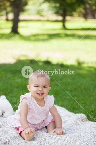 Cute baby sitting on blanket at park