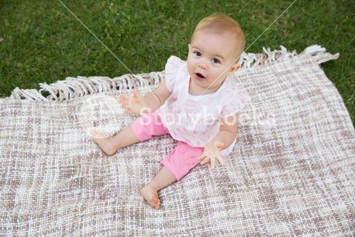 Portrait of a cute baby on blanket at park