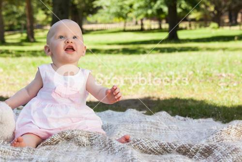 Cute baby sitting on blanket at the park
