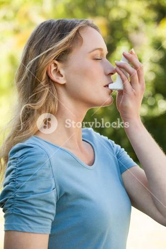 Young woman using asthma inhaler at park