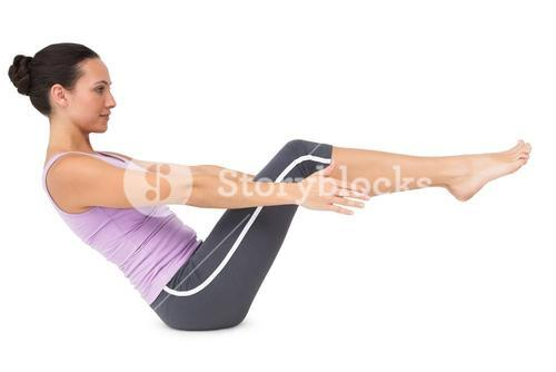 Side view of a fit young woman doing the boat pose