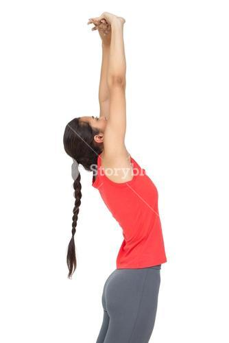 Side view of a sporty young woman stretching hands