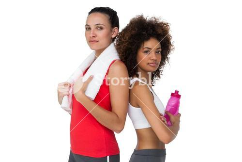 Fit women standing with waterbottle and towel