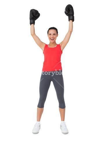 Portrait of a cheerful female boxer raising hands