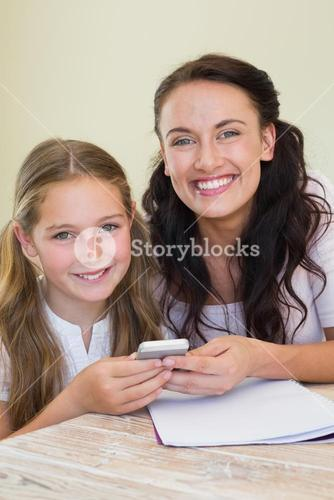 Mother and holding mobile phone at table