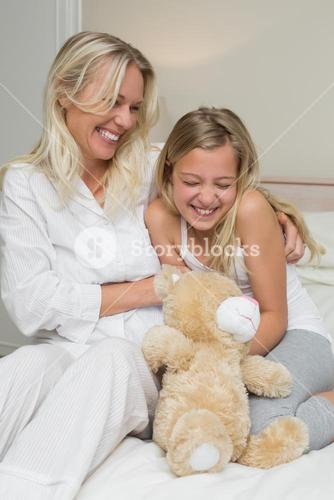 Mother tickling daughter in bed