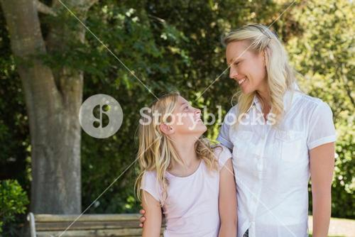 Mother and daughter looking at each other in park