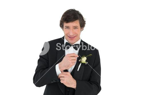 Smiling groom in tuxedo getting ready