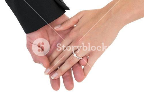 Close-up of bride and groom with hands together