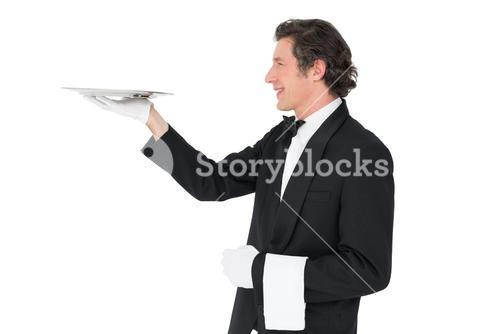 Waiter carrying tray against white background