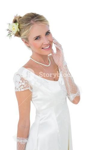 Smiling bride touching cheek over white background
