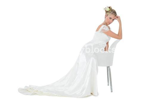Confident bride leaning on chair over white background
