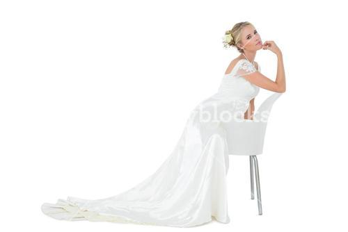 Bride with hand on chin leaning on chair
