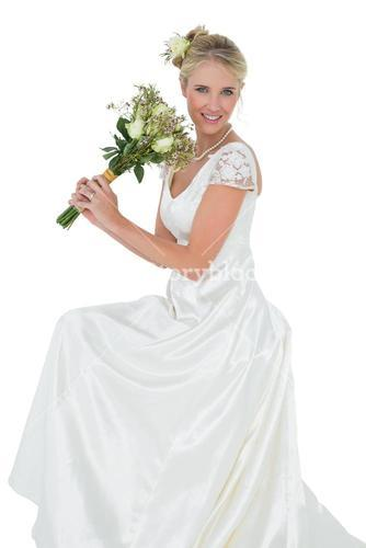 Young bride holding flower bouquet against white background