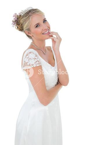 Bride with hand on chin against white background