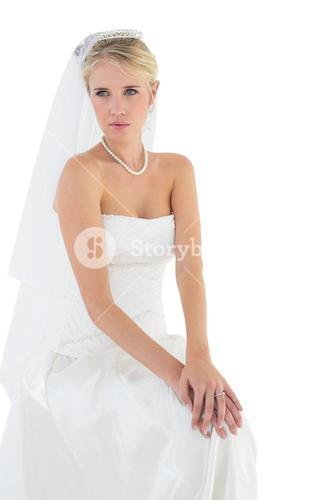Thoughtful bride sitting against white background