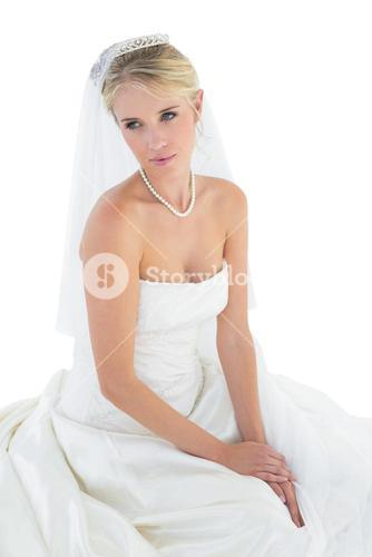 Thoughtful young bride in off shoulder dress
