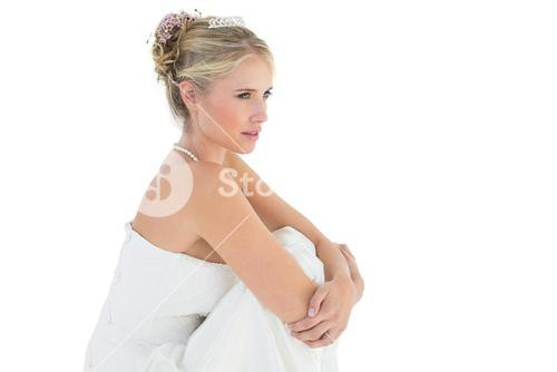 Thoughtful bride hugging knees over white background