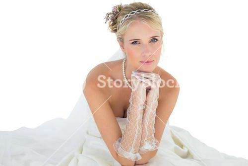 Bride with hand on chin sitting over white background