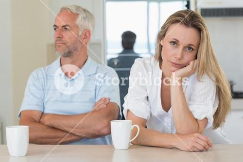 Fed up woman sitting at the counter with her partner