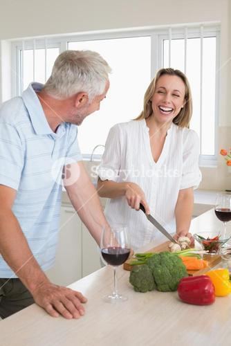 Laughing couple making dinner together