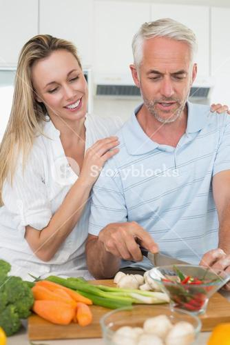 Affectionate couple preparing dinner together