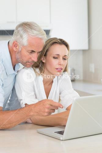 Serious couple using laptop together at the counter