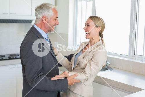 Happy business couple laughing together before work in morning
