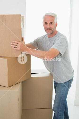 Happy man moving cardboard moving boxes
