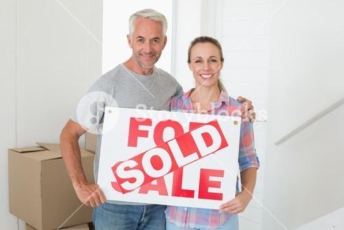 Happy couple standing and holding sold sign