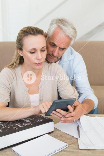 Serious couple calculating their bills at the couch