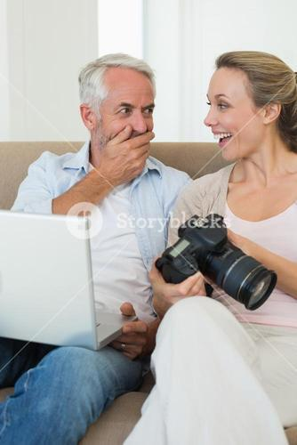 Happy couple viewing their photos on the laptop
