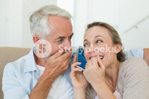 Happy couple listening to phone call together on the couch